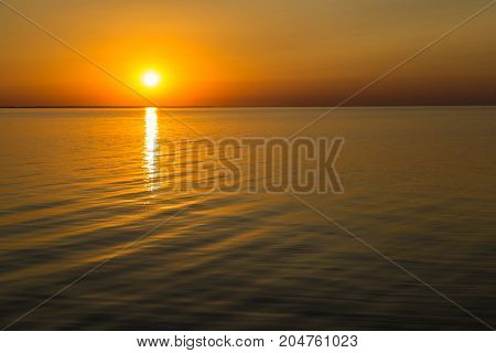 Beautiful orange sunset over the lake. Sun sit down on smooth water surface. The solar path. Siwash lake. Ukraine