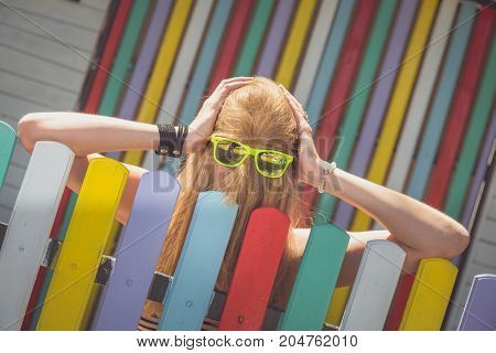 Hipster girl with sunglasses and hair over her face next to colorful fence. Fashion concept