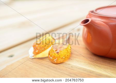 Honey caramel candy lollipop with sticks and teapot on wooden background. Products display, view.