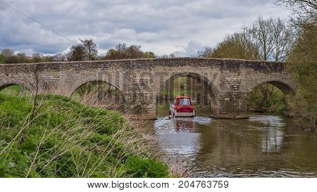 Teston bridge over the river medway in Kent with a small boat going through one of the arches