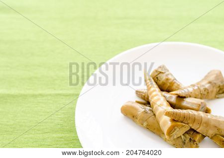 Bamboo Shoots In White Dish On Green Table Background