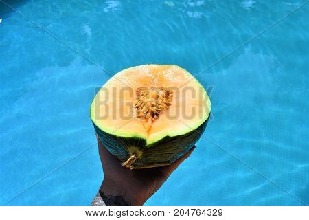 melon in the hand over the pool. juicy melon. summer day. fruits pool. fruits and sea. vacation time. swimming pool. swimming pool food. healthy fruit. spa vacation. travel concept. relax time.