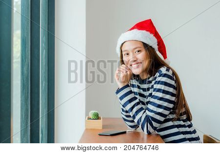 Asian teenage girl with Christmas hat and smile face resting her chin on her hands and drink coffee near window in xmas party at cafe Celebrate New year and Christmas holiday concept