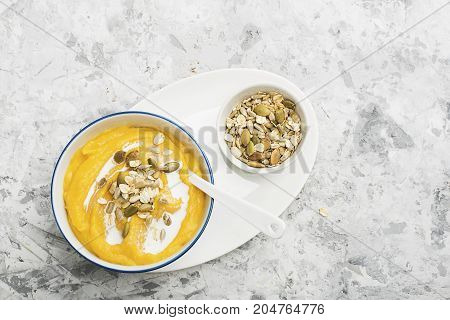Pumpkin and apple cider soup with a topping of crispy toasted pumpkin seeds, sunflower seeds and oat flakes in a serving bowl on a light background. Top View