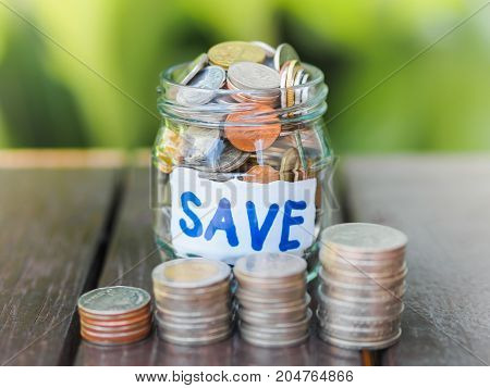 Retro abstract money saving women hand holding glass jar coins with green tree background.