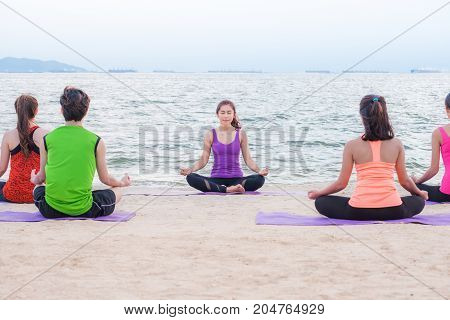 Yoga training class at sea beach in evening sunset Group of people doing lotus poses with clam relax emotion at beachMeditation poseWellness and Healthy balance lifestyle.