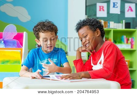 Two boy kid sit on table and reading tale book in preschool libraryKindergarten school education concept.