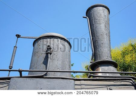 Smoke stack of an old locomotive against sky