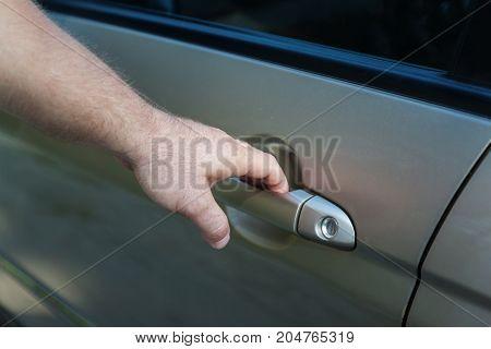 a man's hand opens the car door.