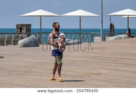 Father Carries His Baby On Tel-aviv Wooden Port Promenade