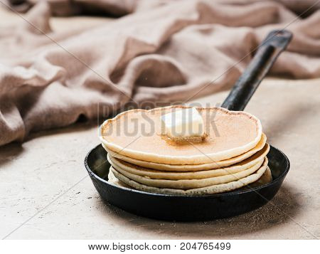 homemade pancakes with butter in iron cast. Stack of pancakes on brown concrete background. Close up.