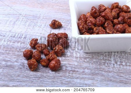 Sugared Hazelnuts in a white bowl on a wooden background. Hazelnuts in sugar glaze. Selective focus