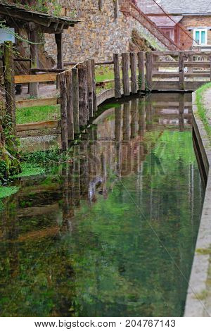 The fence which is reflected in water. A fragment of constructions of the Spanish village a wooden fence a stone wall and reflection in green water of the channel in cloudy summer day