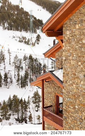 Fragment of the stone house at a mountain in the winter. The house at the bottom of an alpine skiing in Andorra. Winter a it is covered with snow on the mountain trees
