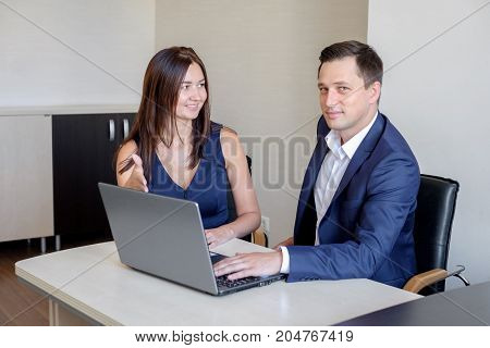 Business people discussing ideas at meeting using laptop in the office.