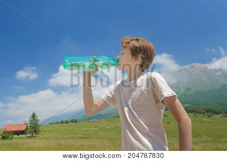 Thirsty boy drinking clear water from battle in his hands high in Italian Alps