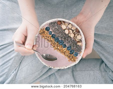 Eating healthy breakfast bowl. Buckwheat smoothie porrige, fresh berries, seeds and nuts, bee pollen in white ceramic bowl in woman hands. Clean eating, dieting, detox, vegetarian food concept