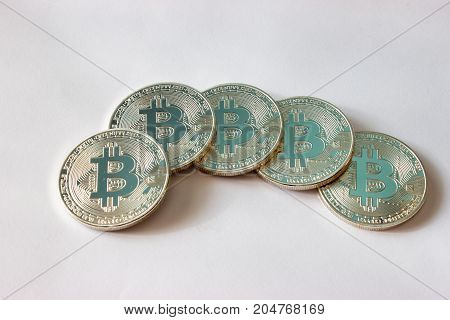 On a grey background are blue silver coins of a digital crypto currency Bitecoin.