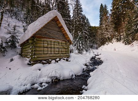 wooden building near the stream in snowy forest. lovely winter scenery great place for hiking in fine weather