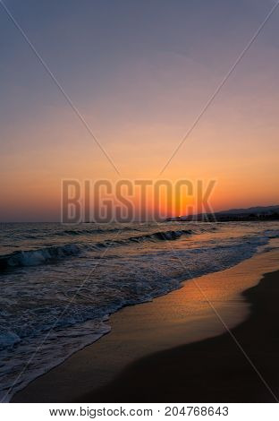 View on a amazing Sunset at the Beach. Close-up of a beautiful deserted Beach in front of a warm Sunset. Travel and Beach Backgrounds.