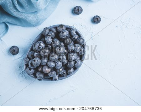 Blueberries in plate on blue background. Fresh picked bilberries close up. Copyspace. Top view or flat lay