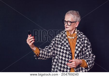Stylish and elegant elderly woman in glasses makes selfie on a black background.