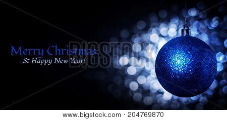 Christmas blue ball, blue bokeh and inscription Merry Christmas