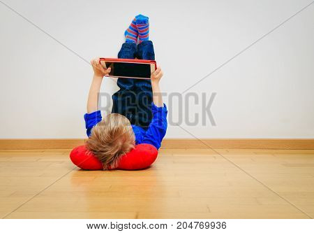 little boy looking at touch pad, home learning and comfort