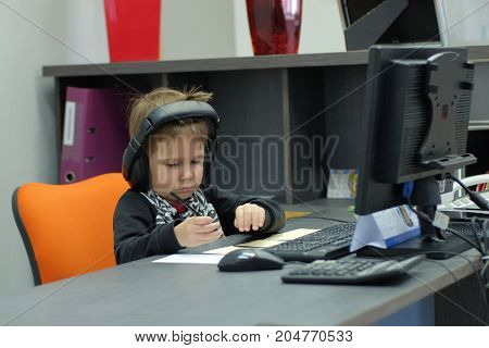 Little boy with headphones sitting at computer in office and makes notes.