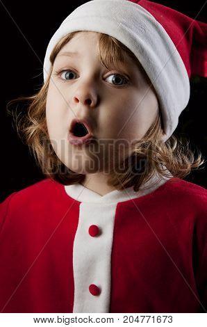 Little caucasian girl dressed as Santa Claus. Close-up portrait on black background