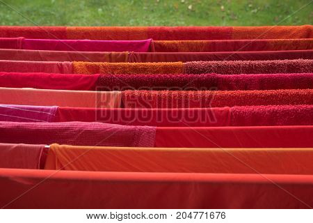 laundry rack in the garden with drying red clothes and towels. Selective focus.