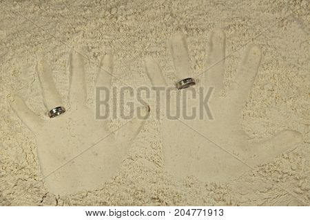 Imprint his and her palms with wedding rings/ Imprint his and her palms with wedding rings in light sand.