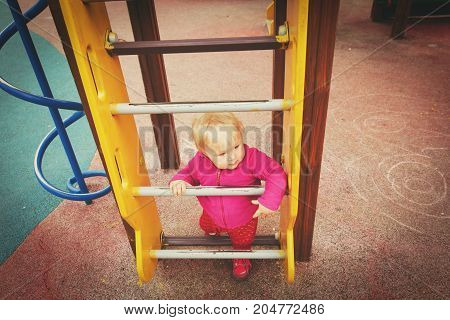 cute little girl playing on playground outdoors, daycare activities