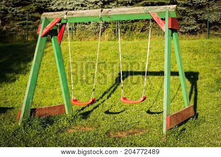 Garden with children's swing. Outdoor playground with swing.