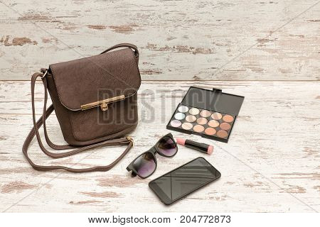 Little brown ladies handbag sunglasses smart phone eyeshadow palette and lipstick on wooden background. fashion concept poster