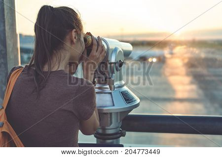 Girl at the airport window looking outside through a telescope