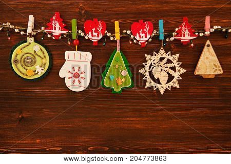 Wooden And Felt Colorful Christmas Decorations And Christmas Lights On A Rope On The Brown Wooden Ba