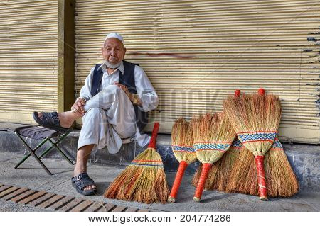 Fars Province Shiraz Iran - 18 april 2017: The old man is selling brooms on a city street.