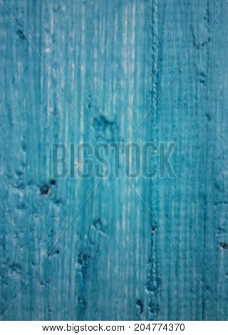 On an old wooden or stone wall the blue paint has peeled off. The paint on a wall is located by rough strips is light grey and blue
