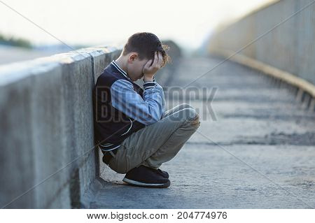 young homeless boy crying on the bridge poverty city street negative emotion