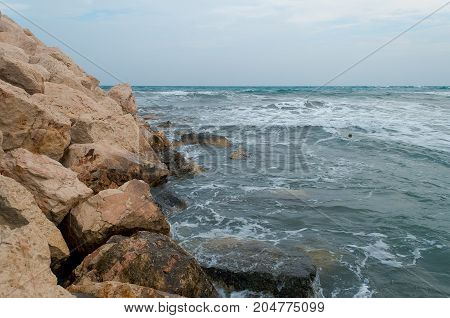 Sea surf during a storm, cloudy weather, gray ocean. Sea waves on the shore.