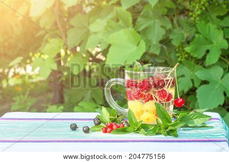 Cherries red and yellow in a glass mug currant mint leaves in sunlight
