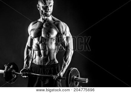 Studio portrait of topless bodybuilder performing biceps exercise with concentrated face over black background with smoke and light. Cutout.