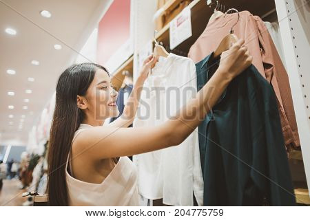 Young Asian Woman Looking at Clothes Hanging on the Rail Inside the Clothing Shop.