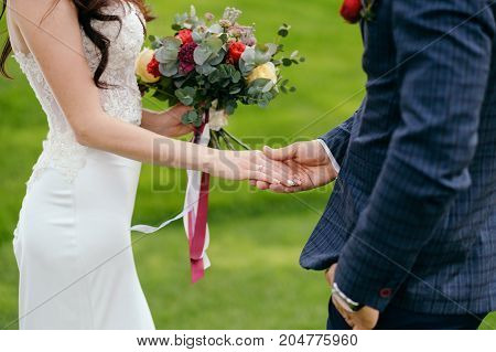 Bride holding colorful wedding bouquet with ribbons standing with groom on the green background