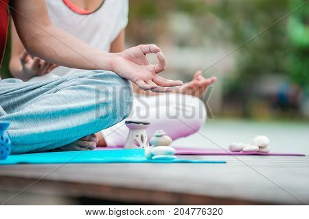 Men and women are sitting in a yoga posture exercise Central Park on a clear day so that the health of their bodies strong.