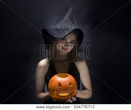 Cheerful witch with pumpkin on black background