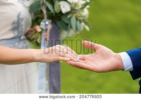 Bride holding wedding bouquet with ribbons standing with groom on the green background