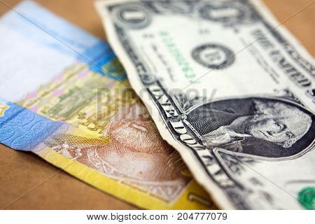 One Ukrainian Hryvnia and one US dollar. American and Ukrainian money.