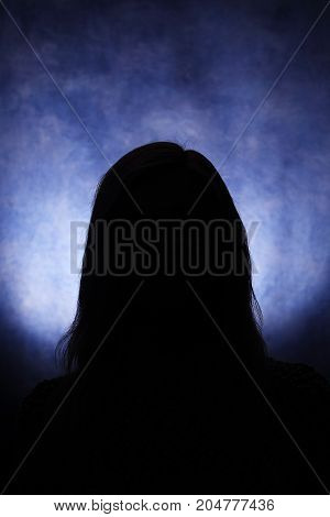 Silhouettes of a female head on a blue background